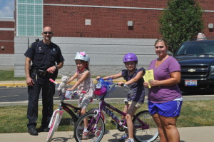 Officer Justin Brewer, Dariview owner Shelley Shupp, and students from Gilles-Sweet School